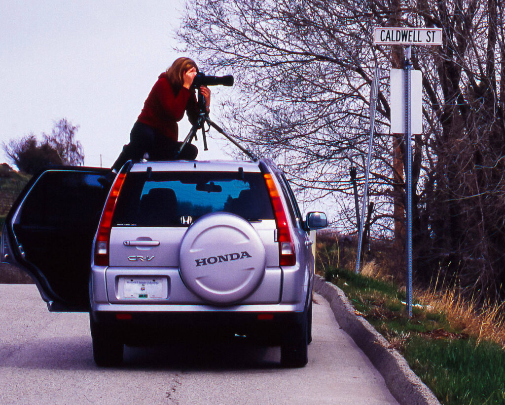 Photography Laura Tucker on top of SUV taking pictures
